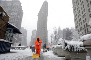 Workers clean snow off a sidewalk in front of the Flatiron building during a late season nor'easter in New York