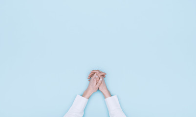 Hands clasped on light blue background