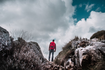 Rear view of man standing on mountain against cloudy sky