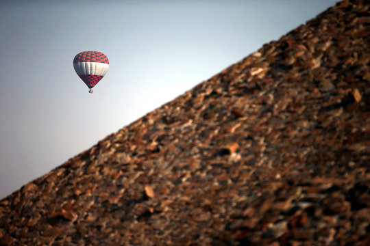 A hot air balloon floats above the Pyramid of the Sun during the spring equinox in the pre-hispanic city of Teotihuacan on the outskirts of Mexico City