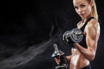 Sporty beautiful woman doing fitness gym exercising at black background to stay fit.
