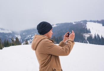 A young guy takes a picture of a mountain landscape on a cellphone