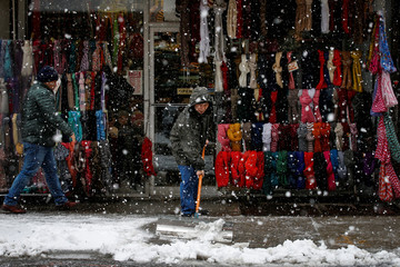 A man clears snow from the sidewalk a winter nor'easter storm in the Chinatown area of New York