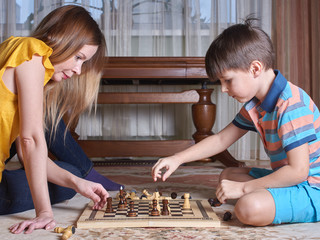 Mother and son are playing chess at home. They are on a floor.