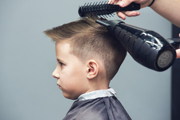 Barber is using hairdryer and hairbrush to make a styling to a Caucasian boy.