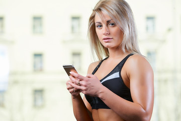 Fit blond girl in a black tank top and black shorts posing with the smartphone. Window on the background. Attractive young women in a gym.