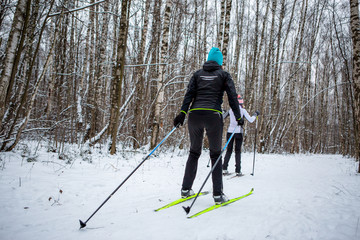 Picture of sports women and men skiing in winter forest
