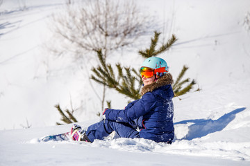 Photo of athlete in helmet with snowboard sitting at fir -tree