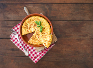Traditional spanish omelette close up,  view from above. Spanish tortilla on a rustic wooden texture with a place for text.