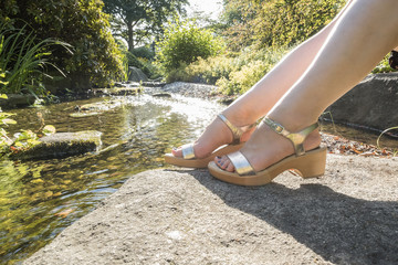 Legs in front of small river in summer