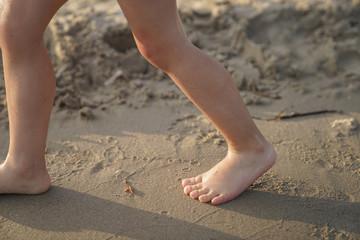 children's feet walk along the sandy beach