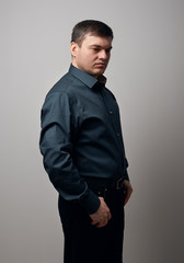 man portrait dressed in shirt and black pants over gray background