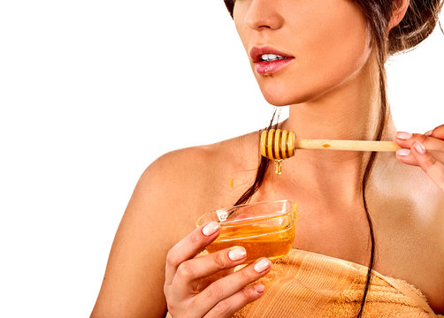 Honey facial mask with fresh fruits for hair and skin on woman head. Close up face of girl with beautiful face hold honeycombs for homemade organic skin and hair therapy. Improvement of skin condition