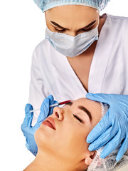 Filler injection for female forehead face. Plastic aesthetic facial surgery by doctor in beauty clinic. Beauty woman giving njections. Doctor in medical gloves with syringe. Acne Removal.