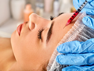 Filler injection for female forehead face. Plastic aesthetic facial surgery by doctor in beauty clinic. Beauty woman giving njections. Doctor in medical gloves with syringe. Wrinkle removal. Facelift.