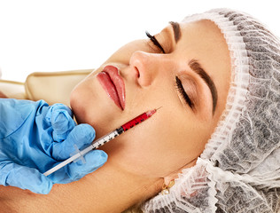 Filler injection for female face. Plastic aesthetic facial surgery and in clinic. Beauty woman giving injections in cosmetology room. Doctor in medical mask. Facelift.
