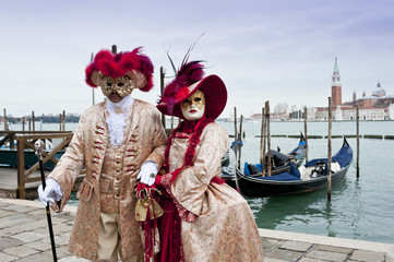 Couple of carnival masks in St. Mark's Square in Venice. In the background the church of San Giorgio.Italy