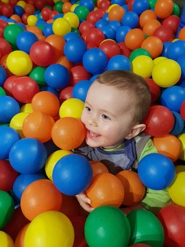 Little boy with colourful balls in a soft play area