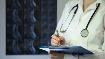 Surgeon writing down patient diagnosis in medical records near X-ray scan