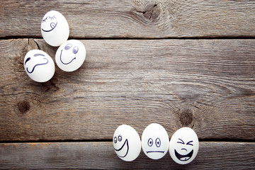 Eggs with funny faces on grey wooden table