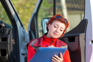 Paramedic female writing on clipboard at emergency car