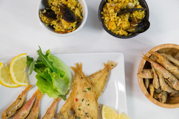 Fried fish and rice with mussels on dish with lemon and salad. Typical sicilian food