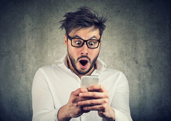 Shocked man having great news on phone