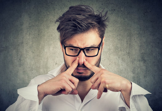 man pinches nose with fingers looks with disgust something stinks bad smell