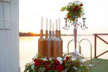 Wedding decor - beautiful installation at the table by the sea: candles, bottles, statuette
