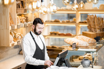 Handsome bread seller working with cash register in the small and cozy store with bakery products