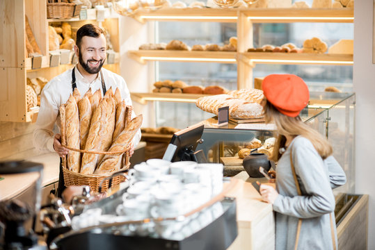 Handsome bread seller with basket full of baguettes and female customer in the beautiful store with bakery products