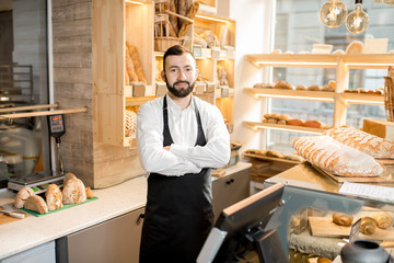 Portrait of a handsome seller in uniform standing in the small and beautiful store with bakery products