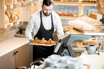 Handsome bread seller with croissants in the small and cozy store with bakery products