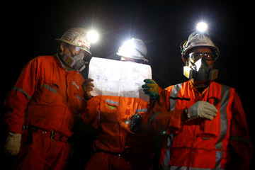 Miners inspect a document inside 'El Teniente' copper mine of Chile's state copper giant Codelco in Rancagua