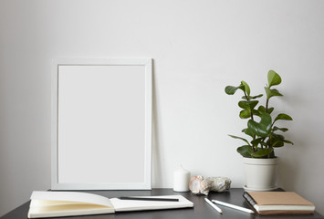 Modern workspace: open sketchbook with white blank pages, pencils, photo frame, decorative plant pot and candle on dark desk. Workplace of creative freelancer. Inspiration, creativity and lifestyle