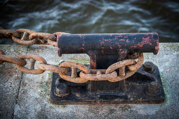 Bollards in the harbor with a heavy, rusty, iron,steel chain. Strong security