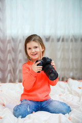 beautiful happy little girl sitting on bed and using a camera. Home, indoors concept. Lifestyle