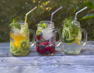 Jars with fruit infused water in summer garden