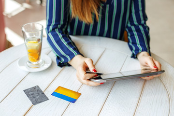 Girl who buys online with a tablet and a credit card. The concept of online shopping, lifestyle, business.