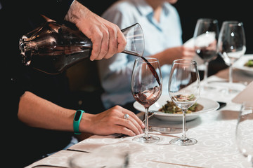 sommelier pouring champagne into glass at wine tasting