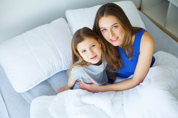 Beautiful mom and daughter are hugging, looking at camera and smiling while sitting on bed at home