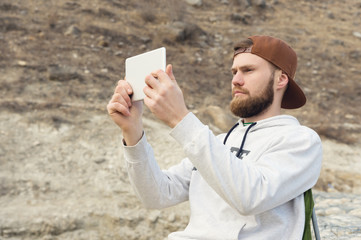 Hipster with a beard in a cap and a sweatshirt with a tablet in his hands takes pictures on a tablet while being outdoors