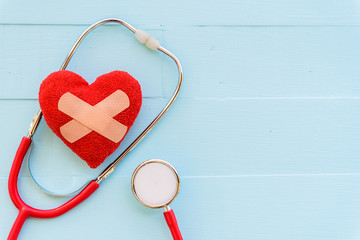 World health day, Healthcare and medical concept. Red heart with Stethoscope on Pastel white and blue wooden table background texture.