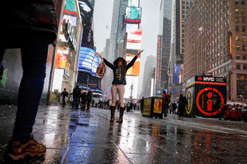 A woman poses for a photo in the snow during a winter nor'easter storm in Times Square in New York