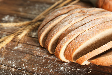Cut bread and wheat spikes on table