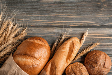Freshly baked bread products on wooden background