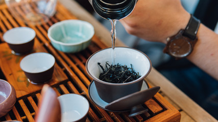 Brewing Chinese tea in ceramic gaiwan during the tea ceremony close-up. Gaiwan and other tea tools for the ceremony