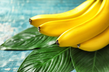 Fresh ripe bananas with leaves on table