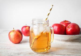 Mason jar with fresh apple juice on wooden table