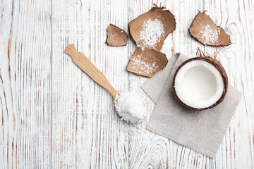 Composition with fresh coconut flakes on wooden background, top view